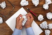 stock photo of storyboard  - Crumpled paper and businessman tearing up another paper ball for the pile - JPG