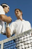 Low angle view of tennis players holding hands after match