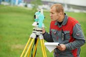 picture of geodesic  - One surveyor worker working with theodolite transit equipment at spring field construction site outdoors - JPG