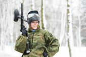 stock photo of cold-war  - happy female paintball extreme sport player wearing protective mask and comouflage clothing with marker gun at winter outdoors - JPG