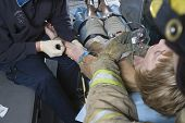 stock photo of pov  - Firefighter and EMT doctor helping an injured patient in ambulance - JPG