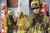 stock photo of fireman  - Portrait of a firefighter talking on radio with colleagues standing in the background - JPG