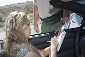 Beautiful young woman writing on traffic ticket with traffic cop standing by her car