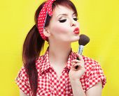 stock photo of rockabilly  - Cute pin up girl applying blusher - JPG