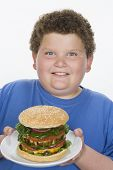 foto of child obesity  - Obese teenage boy with a hamburger isolated over white background - JPG
