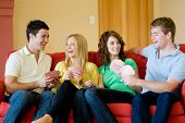 picture of playing card  - Four friends sitting at home on the sofa playing cards - JPG