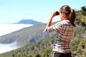 Hiker looking in binoculars enjoying view above clouds during hiking trip. Young Asian woman on hike