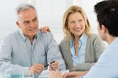 stock photo of wifes  - Portrait Of Happy Senior Couple Talking With A Young Man - JPG