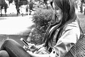 stock photo of long distance relationship  - Pretty young woman using mobile phone internet - JPG