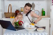 pic of housekeeper  - Young mother with little child sit at the dining table in the home kitchen - JPG