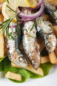 Grilled sardine wish served with french fries and lettuce
