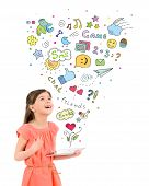 image of fascinator  - Happy cute little girl in red dress holding apple ipad in hand and fascinated looking up at the colorful icons of different entertainment apps - JPG