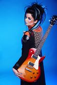 stock photo of emo  - Back of Rock emo girl posing with electric guitar isolated on blue background - JPG