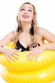 picture of monokini  - Ecstatic girl in swimsuit with two yellow rubber rings looking up isolated on white background - JPG