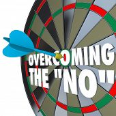 The words Overcoming the No on a dartboard with one dart hitting the center bulls-eye to win the gam