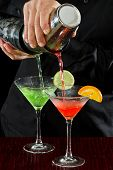 image of bartender  - professional bartender pouring two martinis at the same time in a fluid motion - JPG