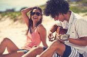 picture of couple sitting beach  - Cute hispanic couple playing guitar serenading on beach in love and embrace - JPG