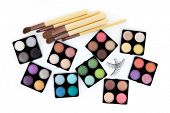 Various eyeshadow palettes, fake eyelashes and cosmetic brushes, isolated on white