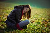 image of ordinary woman  - young smiling ordinary  woman sit on grass on field - JPG