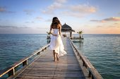 Young woman in white clothes walking on a pier on Maldives