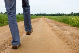stock photo of dirt road  - a man going on the broken road - JPG