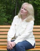 stock photo of middle-age  - Middle aged woman enjoys a quiet time in the park - JPG