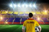 stock photo of football pitch  - Colombia football player holding ball against stadium full of colombia football fans - JPG