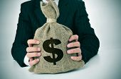 foto of holding money  - a man wearing a black suit holding a burlap money bag - JPG