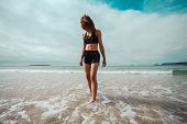 stock photo of wet feet  - An athletic young woman is walking on the beach and is getting her feet wet in the surf - JPG