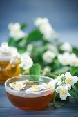 stock photo of jasmine  - jasmine tea in a teapot with a branch of jasmine on a wooden table - JPG