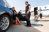 picture of bodyguard  - Full length of bodyguard helping elegant woman stepping out of car at airport terminal - JPG