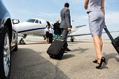 picture of jet  - Business partners with luggage walking towards private jet at terminal - JPG