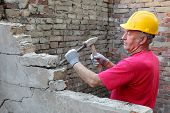 image of chisel  - Construction worker demolishing old brick wall with chisel tool and hammer - JPG