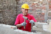 image of chisel  - Construction worker demolishing old brick wall with chisel tool and hammer real people - JPG