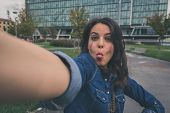 stock photo of long tongue  - Pretty girl with long hair takes a selfie in the city streets - JPG