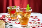 stock photo of cocktails  - Glasses of Mint Manhattan cocktails surrounded with Christmas ornaments and decorations - JPG