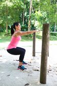 foto of squatting  -  Beautiful strong woman doing squat exercise by the exercise bar in the park - JPG