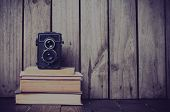 stock photo of  media  - Vintage medium format camera and a stack of books on a wooden board hipster style - JPG