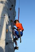 stock photo of climbing wall  - Young boy climbing a rock wall outside - JPG