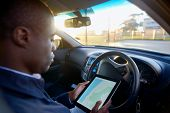 picture of gps navigation  - Man using GPS navigation on tablet computer to find address to drive in his car - JPG