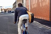 picture of commutator  - Black african mad riding bicycle in urban city commuting with speed and hipster trendy transportation - JPG