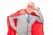 stock photo of tin man  - Shocked senior superhero with a tin can phone isolated on white background - JPG