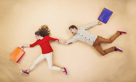 pic of runaway  - Young couple in Christmas hats having fun running with shopping bags against the beige background - JPG