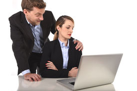 image of inappropriate  - young attractive businesswoman suffering sexual harassment and abuse of colleague or office boss touching her at work with excessive familiarity in work relationship concept - JPG