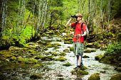 stock photo of binoculars  - Man hiking and looking through binoculars in forest - JPG