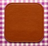 stock photo of blank check  - Blank leather brown label on checked background - JPG