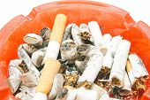 stock photo of butts  - butts in red ashtray on white background closeup - JPG