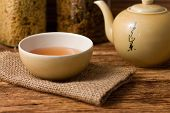 image of kettles  - Horizontal photo of Chinese tea in cup with kettle on right placed on jute cloth and herbs in background placed on old worn wooden board - JPG