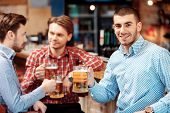 stock photo of mans-best-friend  - Spending time with best friends. Selective focus on handsome young man toasting with beer and smiling while sitting with the friends in beer pub ** Note: Shallow depth of field - JPG
