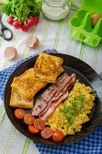stock photo of scrambled eggs  - Scrambled eggs with bacon and French toast on a cast iron pan